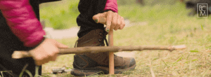 Woman Rubbing Sticks Together to Make Fire