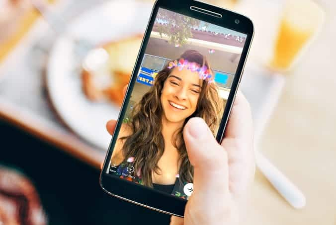 woman's hand holding a mobile phone displaying a woman using Instagram face filter.