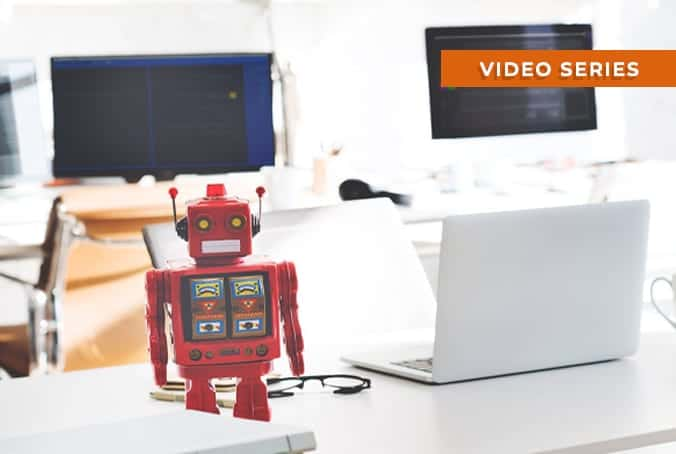 a red robot on a desk with computers in background