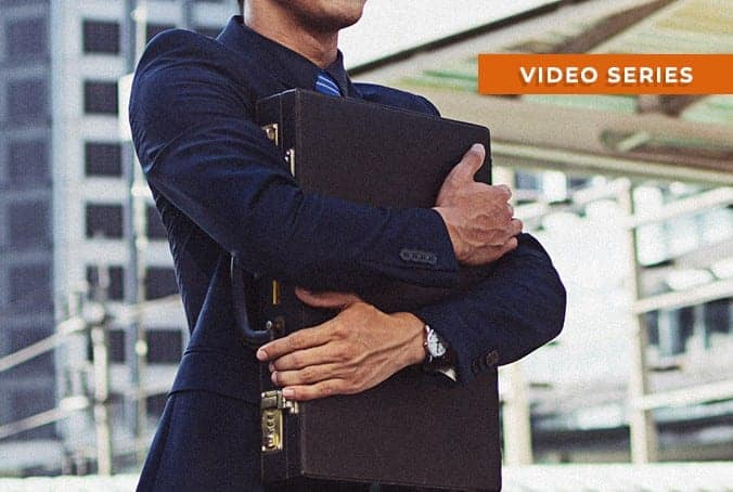 man in suit hugging briefcase