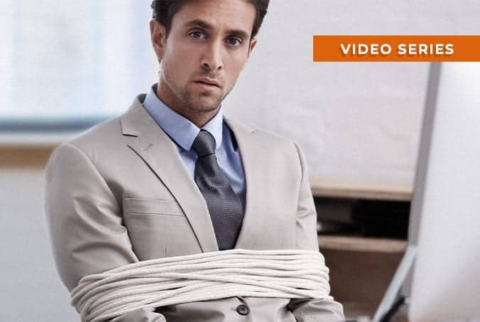 businessman in office tied up in rope at his desk